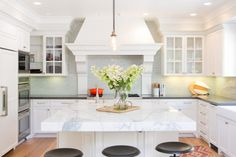 A large center island with a marble top ups the prep space and elegance factor of the kitchen, illuminated by graceful pendants.