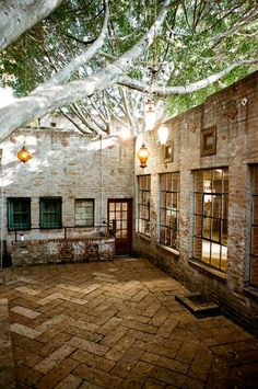 Brick house with courtyard. Love the lights.