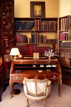 A wooden desk with gold molding is surrounded by painted room dividers and full bookshelves