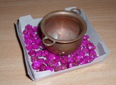 A decoration with hot pink beads and a big pot in the middle.