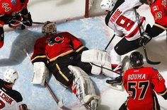 """siphotos: """" Calgary goalie Miikka Kiprusoff lies down in the crease to cover the puck as New Jersey's Zach Parise looks for a rebound during a Flames-Devils game earlier this month. Kiprusoff came in. Ice Hockey Teams, Hockey Players, Fire And Ice, Calgary, Nhl, Football Helmets, Awesome, Sports, Hs Sports"""