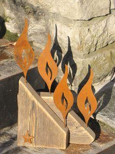 4er Set Edelrost Flammen auf Holz  4 kleine Flammen zieren den abgeschrägten Holzblock, der mit einem kleinen Stern aus Edelrost verziert ist.  Eine schöne Dekoration, die das ganze Jahr eine Bereicherung in Haus und Garten ist,  die aber auch als Adventskranz seine Verwendung findet.  Unikat aus eigener Herstellung.  Größe:      Höhe: 43 cm     Breite: 24 cm     Tiefe: 8 cm  Preis: 15,- €