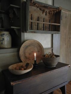 Old wood table, bowls and candle. Simply prim.