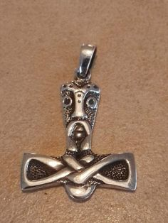 """Thors hammer """"watching you"""" Sølv: 280 kr Bronze: 110 kr 39 x 27 mm -   Det vigtigste nordiske symbol, fundet  i hele vikingernes område. Mjølner  lammede fjenderne og vendte altid til- bage til Thor, hvilket gjorde ham  uovervindelig. Den blev båret af hedninge som bevis på deres tro på de  gamle guder. Amulet for beskyttelse  og energi. Hovedet viser en kriger- maske, som forstærker hammerens magt og beskyttelsesevne."""