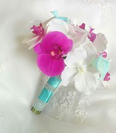 Beautiful Natural Touch Aruba Turquoise Blue Calla Lilies with Natural Touch Fuchsia and White Phalaenopsis orchids accented with bouquet gems
