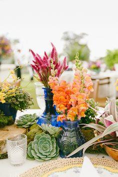 Arranjos estilo rústico chique em vasos azuis, com suculentas, flores coloridas, toras de madeira. Foto: Fernanda Petelinkar