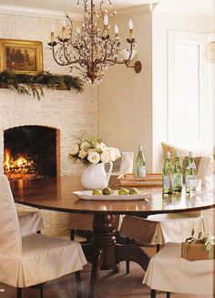 Love the round table and slip covered chairs, of course a fireplace in the dining room helps!