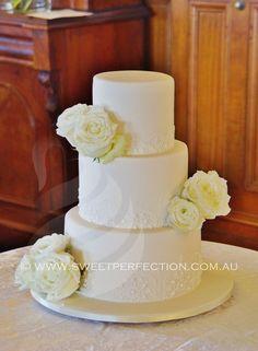 Ivory wedding cake with fresh flowers and lacework.