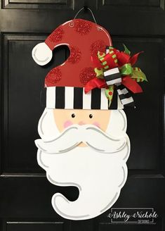 """Ho Ho Ho! Our NEWEST whimsical Santa is a timeless and classy piece, and so much fun with glittered red polka dots on his hat. It would be a beautiful piece adorning your door or as decor inside your home. Handpainted in the USA. Made of 1/4"""" thick wood and painted on the back for a polished look. Size: 33"""" tall x 14"""" wide"""