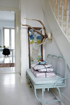 Vintage turquoise bench in entry way paired with natural antlers.