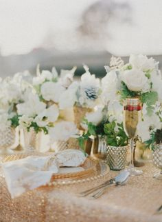 White, touch of green maiden hair fern, silvery dusty miller.  You could always glam up the tables with a gold overlay like this one...