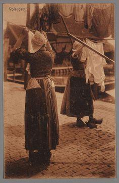 Twee vrouwen in dracht hangen de was op aan de rooplijn. 1905-1920 #NoordHolland #Volendam