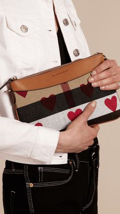 A compact Burberry clutch bag in heart-print Canvas check and leather to keep your phone, lipstick and cards at hand's reach. The design features a detachable leather strap so that it can be worn as a shoulder bag.