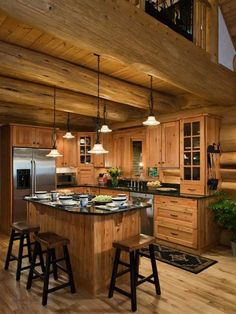 Cabinets match the wood of the walls - dark counters - stainless appliances - pendant lights