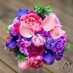 """""""Blooming Colors!"""" vibrant summer bouquet in shades of purple and pink with peonies, roses, and hydrangeas - Peonies are the flower of the season! Timeless, classic, and oh so beautiful. This festive bouquet is the perfect colorful twist for any wedding theme. Accented with bright greenery and many shades of pink and purple this bouquet is sure to match your wedding colors. Fun and fresh look great for indoor or outdoor weddings."""