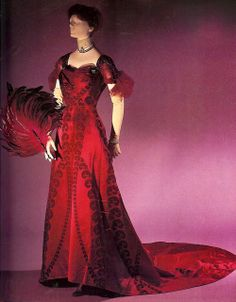 Evening Gown (1908). Description: Red – violet voided velvet patterned in design of ostrich plumes, trimmed with matching embroidered net a...