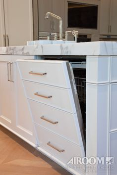 A high-end dishwasher hides inconspicuously behind a drawer façade in the island of this Winnetka, IL kitchen.