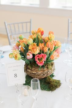 Centerpiece for spring wedding - bright tulips and ranunculuses in basket  {Krystal Balzer Photography}