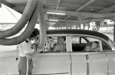 A family in Houston at a drive-in restaurant having cool air piped into their car, 1957.