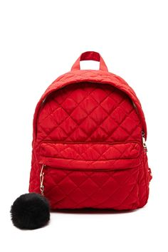 This backpack is crafted from a quilted woven material and features a main zippered compartment, exterior zip pocket, two interior slip pockets, dual straps, and a removable pom pom keychain.