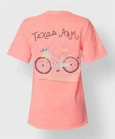 """This 100% cotton Comfort Colors shirt has a pocket on the front with a floral print block ATM and reads """"Aggies"""". The back has the image of a bike with flowers rolling down a street with hearts coming off of it. It reads """"Texas A&M, Aggieland""""."""