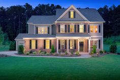 A winding walk leads to a welcoming front porch framed by four pillars. The Glenstone plan by Traton Homes. The Great Oaks Estates community. Acworth, GA.