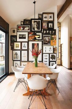 A very full gallery wall with wooden table and eames style chairs in the dining . A very full gallery wall with wooden table and eames style chairs in the dining room Design