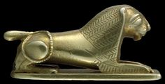 Amulet. Gold couchant lion: the body cast with a hole through the chest to the tail; the rectangular baseplate with curved front edge was made separately. The body is smooth and undecorated except for details of the mane which are chased between parallel lines, and the feathering on the forelegs.       17th Dynasty 1650BC-1550BC (circa). | © Trustees of the British Museum