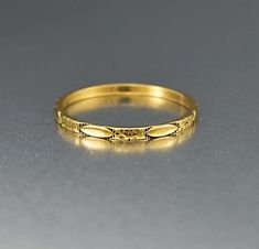 Rendered in a rich 14K yellow gold this wonderful vintage Art Deco ring is the consummate eternity band. Carved all around eternity band style with an orange blossom and oval design. Elegant and classic, the ring is the perfect compliment to an engagement ring or for stacking with others. Materials: 14 karat yellow gol