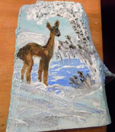 A deer and a winter scene. This is painted on a piece of a maple tree. It is a small ornament size. painted with multi-surface paints.
