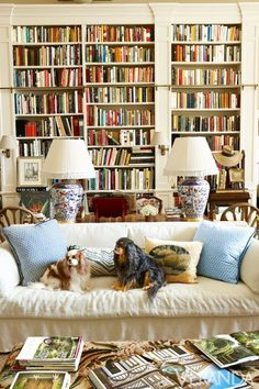 Traditional library by Charlotte Moss.Sofa table w/ 2 lamps, chairs next to table.