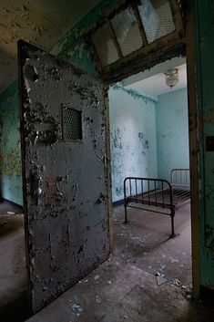 Verden Psychiatric Hospital - A handful of these rooms could be found throughout the building, secured with extra mesh around the observation window, light, and ventilation window. This particular one had a bed bolted into the floor.