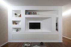 Parete attrezzata con libreria in cartongesso e tv sospesa per salotto a Firenze