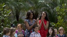 """U.S. First Lady Michelle Obama, center left, and her daughter Malia, center right, clap as they stand with children of U.S. embassy workers after dedicating two magnolia trees and a bench, at a small park beside Ruben Martinez Villena public library in Plaza de las Armas, Old Havana, Cuba, Tuesday, March 22, 2016. The bench bears the inscription in English and Spanish """"A gift to the people of Cuba from Mrs. Michelle Obama, first lady of the U.S., March 2016."""" (AP Photo/Rebecca Blackwell)"""