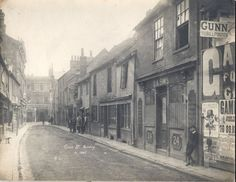 Cross Street, Reading, looking southwards to Broad Street, 1887. On the right, at No. 21, William Fossett, tripe dresser. Nos. 22 and 23 appear to be empty, and No. 24, formerly D. A. Sims, antiques dealer, is boarded up. On the right, a hoarding advertises Gamlen Brothers, hatters, and Gunn, the bill poster. On the south side of Broad Street, part of Nos. 116-117, is the Angel Brewery and Brewery Tap of Ferguson and Sons. 1880-1889 : Reading Borough Libraries Old Pictures, Old Photos, History Of Reading, Reading Berkshire, Genealogy, Roads, Brewery, Empty, England