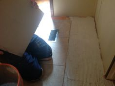 Installing the travertine tile into the mud bed.