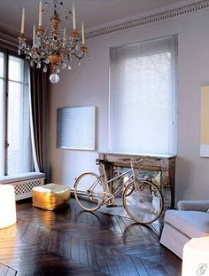 A Paris styled living room complete with a chandelier and a bicycle. Le fab!