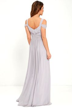 """From posh prom or lavish cocktail party, and from sea to shining sea, the Bariano Ocean of Elegance Grey Maxi Dress will have you in the lap of luxury wherever you may go! Crisp grey Georgette starts this exquisite ensemble off with tank straps (joined by sheer off-the-shoulder straps) that support a fitted bodice with a plunging sweetheart neckline, and elegant ruching details. Additional ruching delicately encircles an empire waistline, while a floor-length maxi with a stunning 31"""" side…"""
