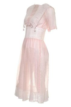 "The details on this 1930's vintage dress are unique and absolutely lovely. It is made in a semi sheer pink cotton voile with tone on tone stripes and beautiful crochet lace. The dress snaps closed in several places and the pretty bodice has crochet dangles off of the lace panels. The beautiful hemline is 4 and 1/2 inches of lace. I would estimate this dress to be a modern day US size 2/4, but please use the measurements as a guide for the best fit. BUST: 32-34"" WAIST: 26&qu..."