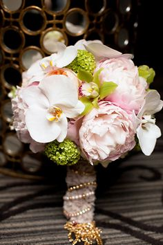 Pink, green, and white bouquet featuring cymbidium and phalaenopsis orchids and peonies.