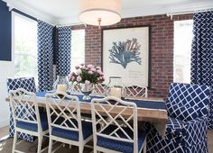 Coastal Blue and White Dining Room. Blue dining room features a linen drum pendant hanging over a salvaged wood dining table lined with white bamboo dining chairs accented with blue cushions against a backdrop of an exposed brick wall lined with a Natural Curiosities Capistrano Seaweed 1 flanked by windows dressed in blue lattice curtains. AGK Design Studio.