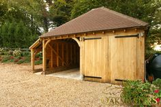 Custom design oak framed garage with one open and one closed bay.