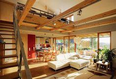 Obývací pokoj dosahuje až pod strop druhého podlaží, prostor na výšku zajímavě člení falešné stropní trámy z masivního dřeva. Z pracovny nahoře na galerii má paní domu výhled do obývacího pokoje i do zahrady před a za domem. By Schaufler-Roskovec
