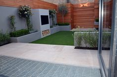 beige limestone paving fake artificial grass lawn outdoor fire place BBQ floating bench hardwood slatted privacy screen and doors bespoke storgae unit London Small Artificial Plants, Artificial Plant Wall, Artificial Flowers, Outdoor Rooms, Outdoor Gardens, Architectural Plants, Contemporary Garden Design, Modern Design, Back Garden Design