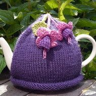 Hand knitted purple tea cosy with crocheted fuchsia flowers and leaves attached. Made with Sirdar Wool Rich Aran which will keep the teapot nice and warm. Will fit a standard 4 - 6 cup teapot. Machine washable on gentle cycle