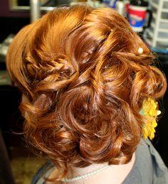 Woven fishtail braids into curly bun.