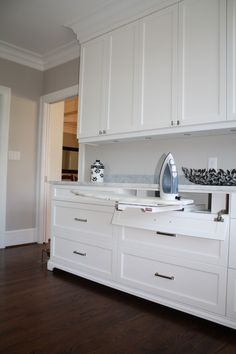 laundry room-cabinets to the ceiling, thick trim, foot detail, drop down drawers for the iron and ironing board