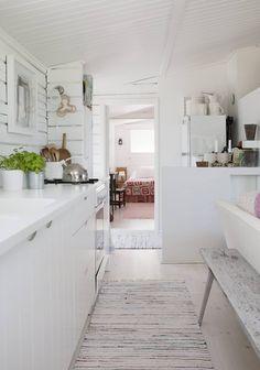 Keittiöstä näkyy makuuhuoneen suuntaan. Pöydän ääressä on pitkät yksinkertaiset penkit. Räsymatot kuuluvat mökkisisustukseen.