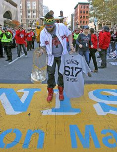 Boston Red Sox left fielder Jonny Gomes sets down the World Series trophy and the 617 game shirt from the dugout onto the Boston Marathon finish line during the Sox World Series parade on Saturday, November 2, 2013. - This makes me tear up a bit!