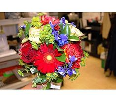 Hand tied bouquet of blue delphinium, cream and red roses, red gerbers, red dahlias and accents of lime green foliage.